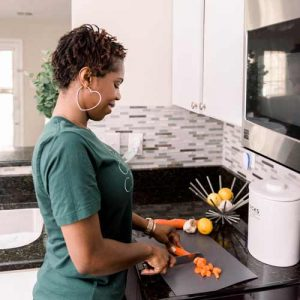 Doula wearing green shirt in the kitchen cutting and preping carrots.